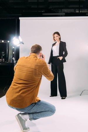 Photo pour Focus sélectif du photographe travaillant avec un modèle élégant en studio photo - image libre de droit