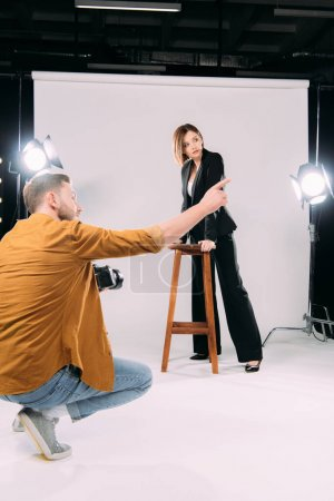 Photographer pointing with finger at beautiful model near chair in photo studio