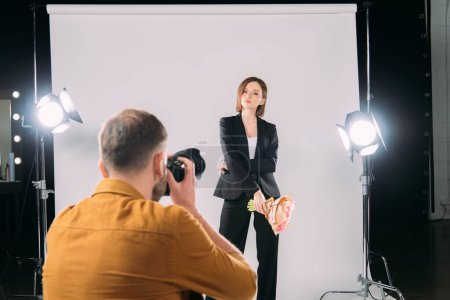 Photo for Selective focus of stylish model with bouquet posing at photographer with digital camera in photo studio - Royalty Free Image