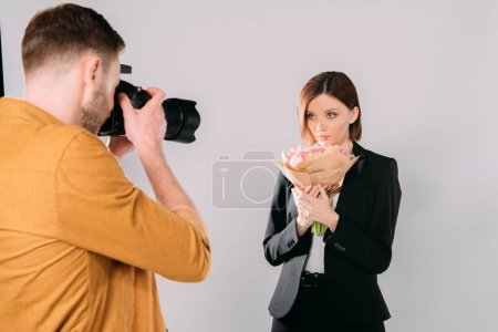 Photo for Photographer taking photo of beautiful model with bouquet of flowers in photo studio - Royalty Free Image