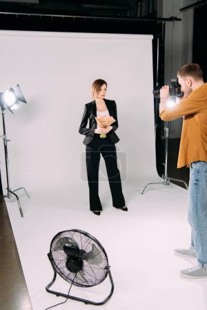 Photographer working with stylish model holding flowers in photo studio