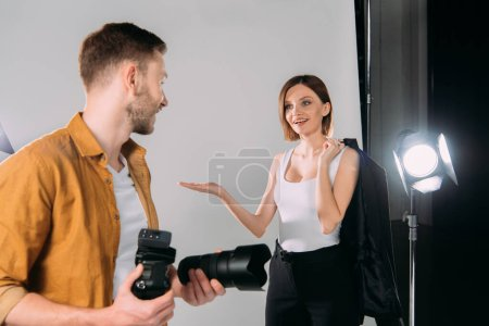 Photo for Smiling model holding jacket and pointing with hands at photographer with digital camera in photo studio - Royalty Free Image