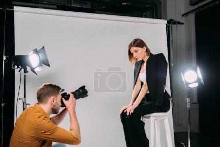 Photo pour Vue latérale du photographe travaillant avec un modèle élégant assis sur une chaise dans un studio photo - image libre de droit