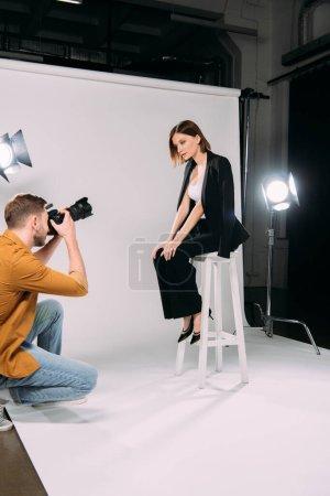 Photo pour Vue latérale d'un beau modèle assis sur une chaise tout en posant chez un photographe avec appareil photo numérique dans un studio photo - image libre de droit