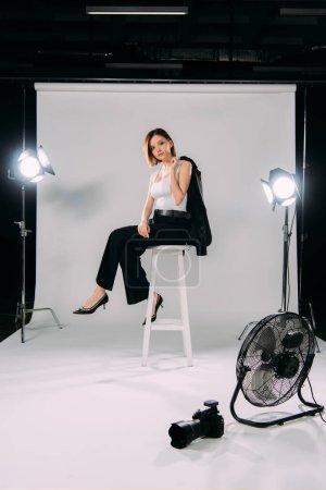 Photo pour Vue latérale du beau mannequin tenant veste tout en étant assis sur la chaise près ventilateur électrique et appareil photo numérique dans le studio photo - image libre de droit