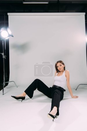 Photo for Beautiful model sitting on floor near floodlights in photo studio - Royalty Free Image