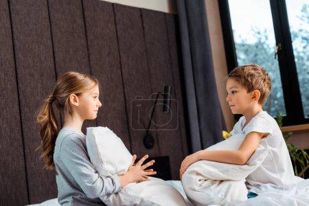 Photo pour Vue latérale de soeur tenant oreiller et regardant frère dans la chambre - image libre de droit