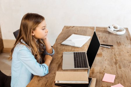Photo pour Vue latérale de l'enfant regardant l'ordinateur portable avec écran vide tout en étudiant en ligne à la maison - image libre de droit