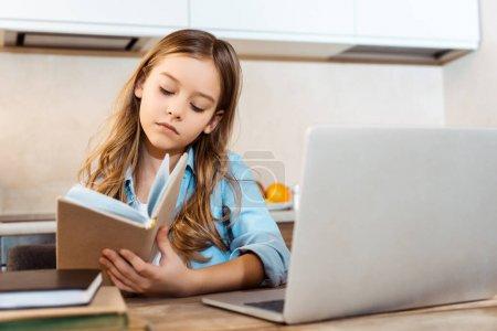 Photo pour Foyer sélectif d'enfant mignon tenant livre près d'un ordinateur portable tout en étudiant en ligne à la maison - image libre de droit