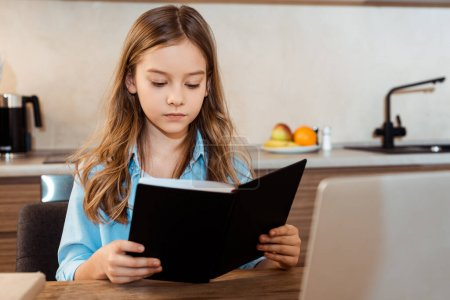 Photo pour Focus sélectif of cute kid reading book near laptop while e-learning at home - image libre de droit