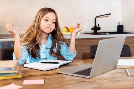 Photo pour Foyer sélectif de gamin confus regardant l'ordinateur portable tout en e-learning à la maison - image libre de droit