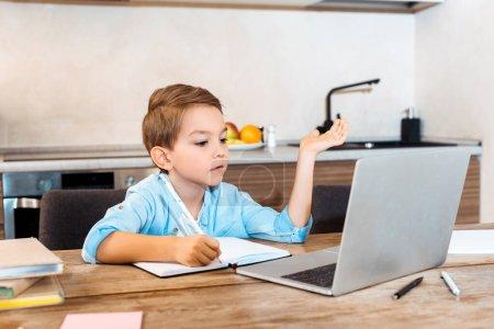 Photo pour Foyer sélectif de l'écriture de garçon dans le cahier et regardant l'ordinateur portable tandis que l'e-learning à la maison - image libre de droit