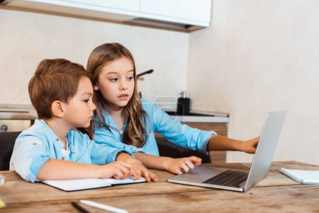Photo for Selective focus of sister and brother looking at laptop while e-learning at home - Royalty Free Image