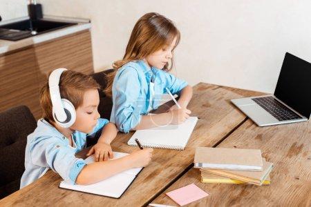 Photo pour Frères et sœurs écrivant dans des cahiers tout en e-learning près d'un ordinateur portable avec écran vierge - image libre de droit