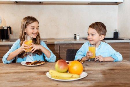 Photo pour Foyer sélectif de frères et sœurs heureux se regardant et tenant des verres de jus d'orange près du petit déjeuner savoureux - image libre de droit