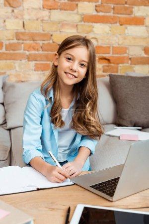 Photo pour Enfant heureux écrit dans un carnet tout en e-learning à la maison - image libre de droit