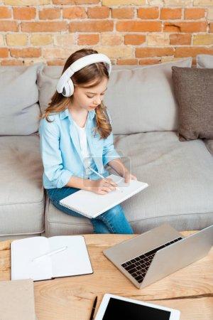 Niedliche Kind in Kopfhörer Schreiben in Notizbuch in der Nähe von Gadgets