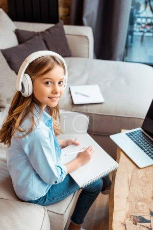 Photo pour Enfant heureux dans un casque sans fil écrit dans un ordinateur portable près de l'ordinateur portable avec écran vide tout en e-learning à la maison - image libre de droit