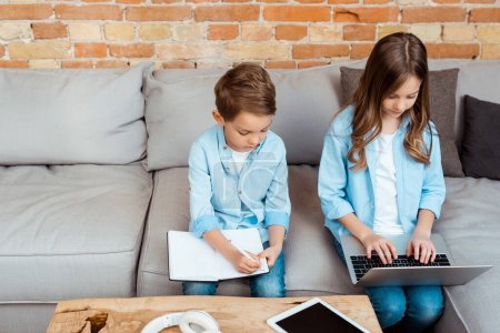 Photo for Cute siblings online studying near gadgets at home - Royalty Free Image