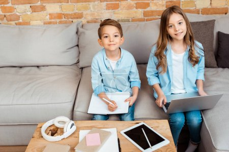 Photo for Happy siblings online studying near gadgets at home - Royalty Free Image