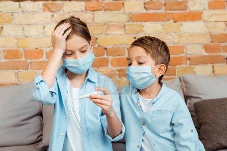 Photo pour Enfant malade dans le masque médical tenant thermomètre numérique près du frère - image libre de droit