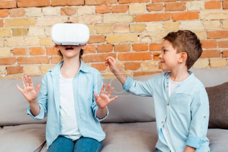 happy brother looking at surprised sister in virtual reality headset