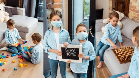 Photo for Collage of siblings in medical masks holding chalkboard with stay home lettering, playing chess and building blocks at home - Royalty Free Image