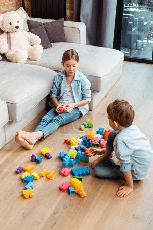Photo for Siblings playing with building blocks and sitting on floor in living room - Royalty Free Image