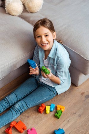 Photo for Overhead view of happy kid holding building blocks and looking at camera - Royalty Free Image