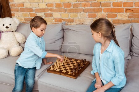Photo for Siblings playing chess on sofa in living room - Royalty Free Image