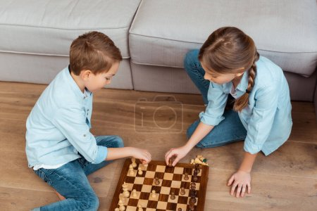 Photo for Overhead view of siblings playing chess on floor in living room - Royalty Free Image