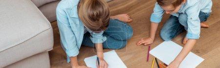 Photo pour Culture panoramique de sœur et frère assis sur le sol et dessin dans le salon - image libre de droit