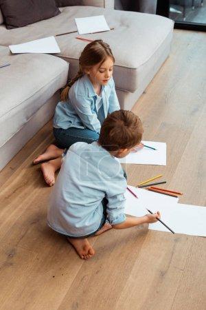 Photo pour Soeur mignonne et frère assis sur le sol et le dessin dans le salon - image libre de droit