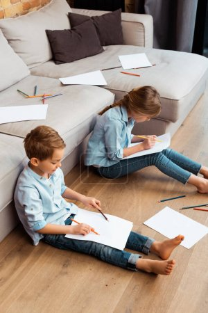 Photo for Cute brother and sister sitting on floor and drawing in living room - Royalty Free Image