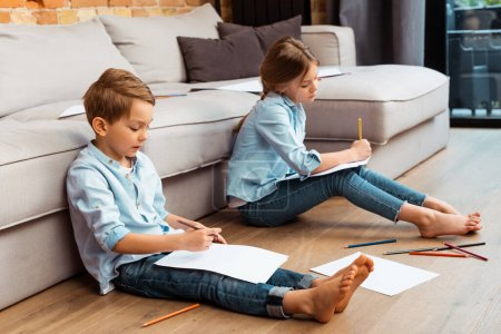 Photo for Cute siblings sitting on floor and drawing in living room - Royalty Free Image