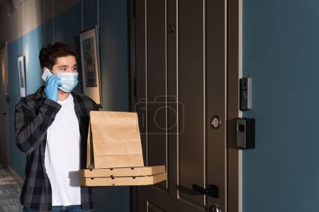 Photo for Courier in medical mask talking on smartphone while holding package and pizza boxes on entryway - Royalty Free Image