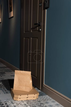 Photo for Package and pizza boxes on floor near door in entryway - Royalty Free Image