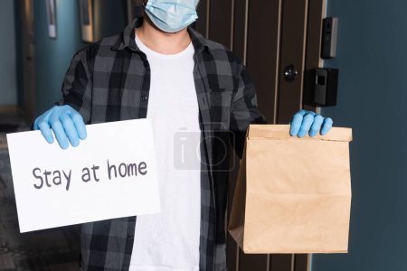 Photo for Cropped view of courier in medical mask holding package and card with stay at home lettering on entryway - Royalty Free Image
