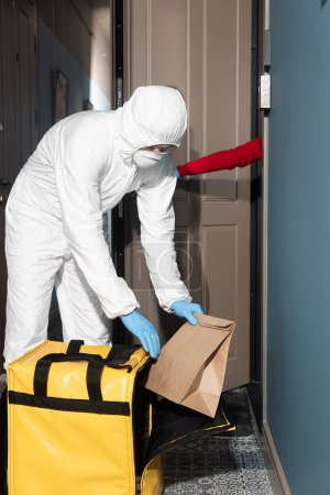 Photo for Delivery man in hazmat suit and medical mask taking package from thermo bag near woman opening door - Royalty Free Image