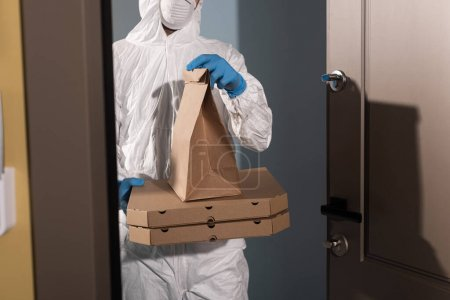 Photo for Cropped view of delivery man in hazmat suit and latex gloves holding package and pizza boxes near open door - Royalty Free Image