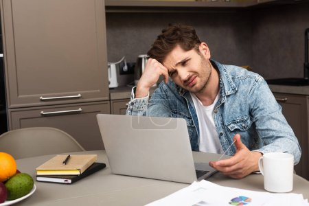 Sad man holding credit card and looking at laptop in kitchen