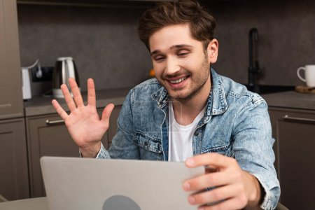 Photo for Selective focus of smiling freelancer having video chat on laptop in kitchen - Royalty Free Image