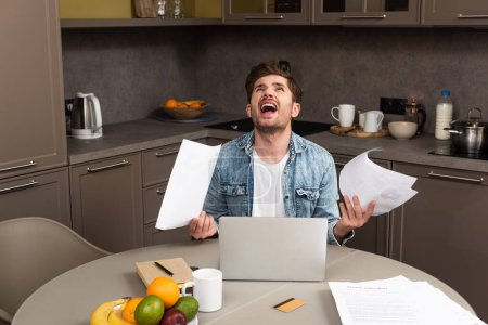 Photo for Irritated man holding papers near credit card and laptop on table in kitchen - Royalty Free Image
