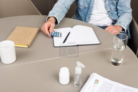 Cropped view of man holding blister with pills near papers, notebook and hand sanitizer on able