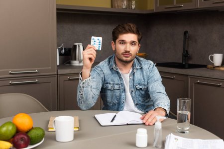 Selective focus of man holding blister with pills near papers, notebook and hand sanitizer on kitchen table