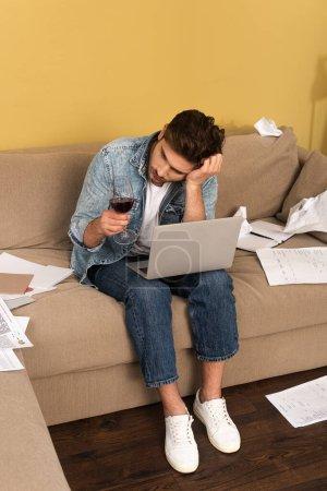 Photo pour Pensée pigiste tenant un verre de vin près d'un ordinateur portable et des papiers sur le canapé à la maison - image libre de droit