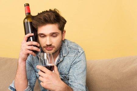 Photo pour Beau homme tenant un verre de vin et une bouteille sur le canapé à la maison - image libre de droit