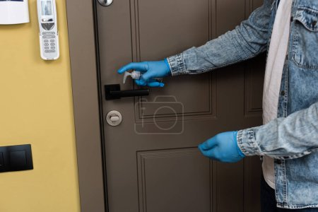 Photo for Cropped view of man in latex gloves using hand sanitizer on door handle - Royalty Free Image