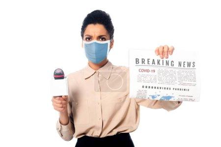 Photo pour Journaliste afro-américain en masque médical avec microphone montrant journal avec des nouvelles de dernière heure covid-19 texte isolé sur blanc - image libre de droit
