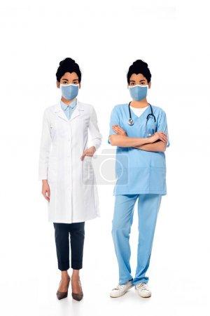 Photo pour Infirmière afro-américaine et médecin avec des visages illustrés dans des masques médicaux sur blanc - image libre de droit